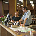 A librarian assists a patron at the Thomas Cooper Library reference desk. Both people are standing at the counter, looking at computer monitors.