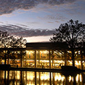View of the front of Thomas Cooper Library in early evening, taken from across the reflecting pool. The lights from the library windows are reflected on the water.