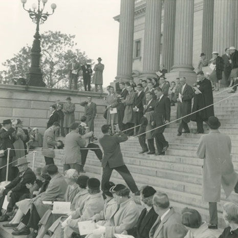 Black and white image of people gathered on steps of South Carolina State House. People in foreground seated on lower steps. In background, a group of people walk down steps, people with cameras photograph them from below.