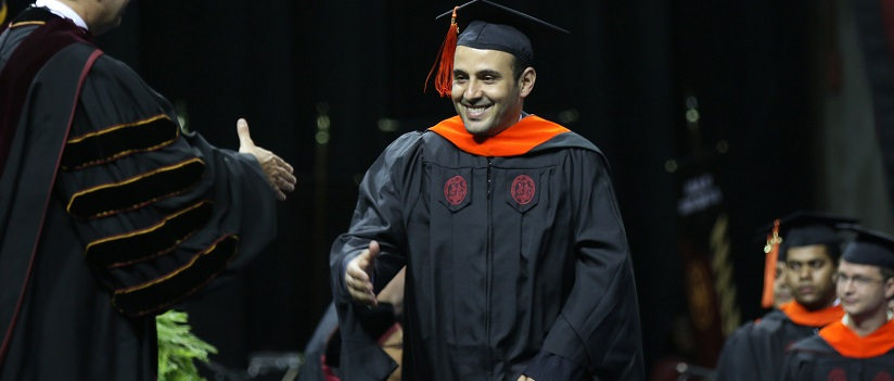 Graduate walks across stage to receive diploma