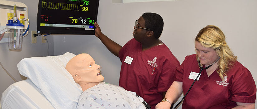 Nursing students receive instruction in the simulation lab.
