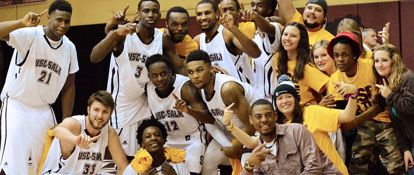 Men's basketball team celebrates a victory.
