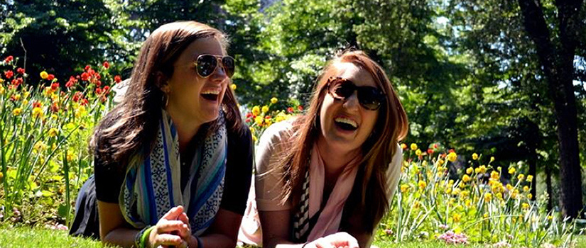 Two female students lay on the grass in front of a bed of flowers on a sunny day, laughing and wearing sunglasses