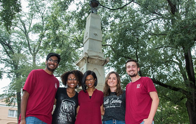 Five students in UofSC T-shirts in front of Maxcy monument