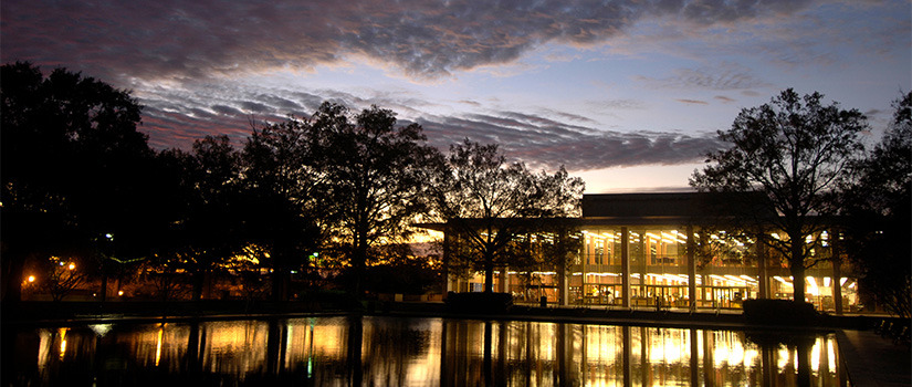 Front exterior of Thomas Cooper Library at dusk, with a darkening sky and the library's interior lights shining on the reflecting pool in front of the building