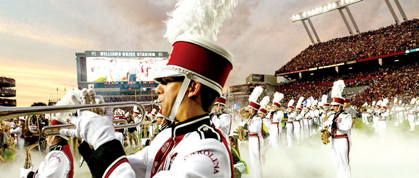 Carolina Band members in uniform and playing their instruments as they stand on the field at Williams-Brice Stadium, with the scoreboard and stands full of fans in the background