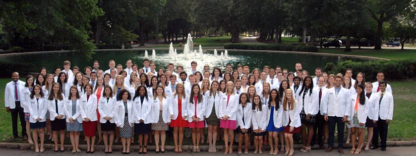 About 100 medical students, each wearing a white lab coat, stand in rows to pose as a group in front of an outdoor fountain