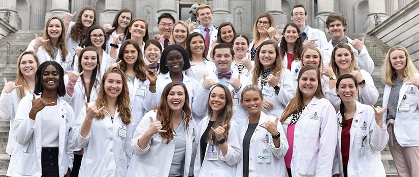 Group of pharmacy students in white lab coats on State House steps