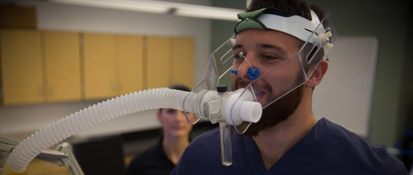 Male Public Health student in dark-colored scrubs demonstrates the use of a breathing apparatus that he wears on his head and face