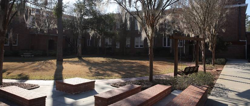Brick benches and trees draped with Spanish moss outside a building on the USC Salkehatchie campus