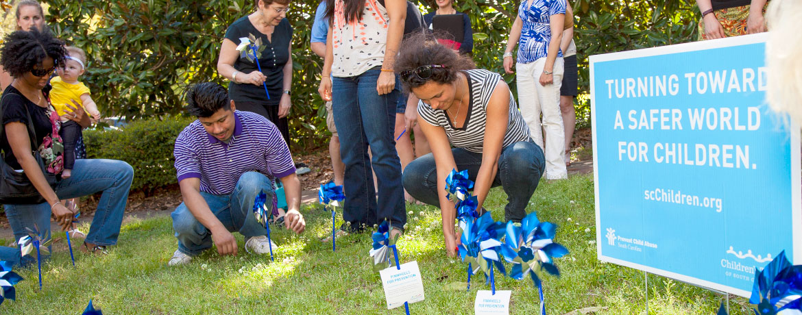 "A group of people, including men and women and one woman holding a baby, place blue-and-silver pinwheels in a grassy area beside a sign that reads ""Turning toward a safer world for children. scChildren.org"""
