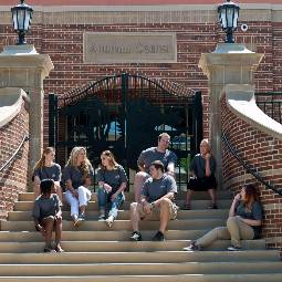 Group of students sitting outside on the steps of the Alumni Center
