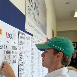 Male student in green baseball cap working at a U.S. Open qualifier tournament, posting scores on a wall poster