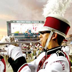 Close-up of Carolina Band member in uniform, playing trumpet, on football field with Williams-Brice Stadium scoreboard in background