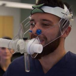 Male student in dark-colored scrubs demonstrates the use of a breathing device on his head and face