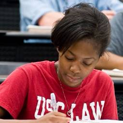 Close-up of student wearing read USC Law T-shirt and taking notes at a desk in a law classroom