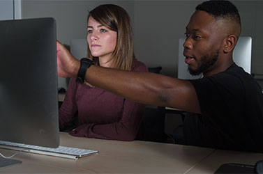 Two students pointing at a computer screen