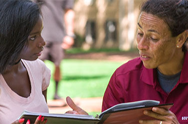 African-American student getting guidance from her professor.
