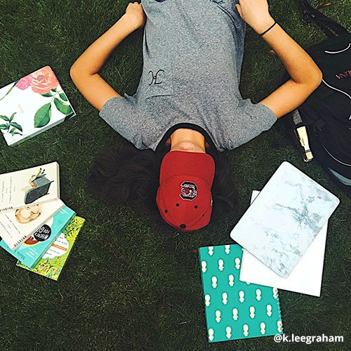 Student lays on ground, Carolina cap covering face, surrounded by books.