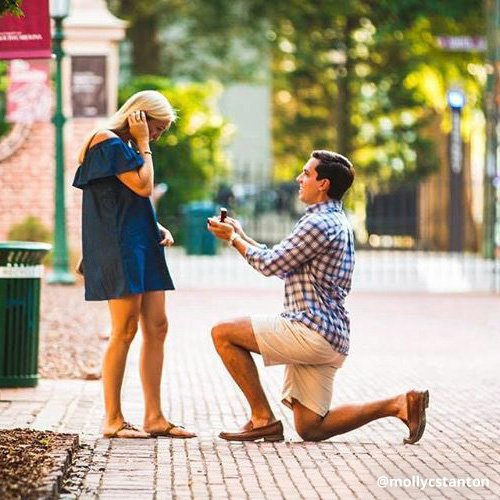 Young man on bended knee proposes to girlfriend on Horseshoe.