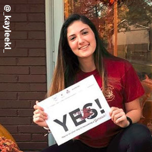 Image provided by @_kayleekl_ of a young woman with long brunette hair in a garnet USC t-shirt, smiling and sitting in front of a glass door holding an acceptance envelope that says, Yes!