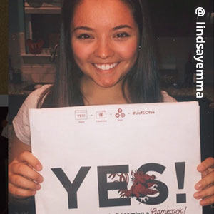 Image provided by @_lindsayemma of a young woman with straight, dark brown hair smiling and holding an acceptance envelope in front of her that says, Yes!
