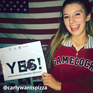 Image provided by @carlywantspizza of a young, blonde woman standing in front of an American flag and wearing a Gamecock pullover with a striped collar. She is smiling and holding an acceptance envelope that says, Yes!