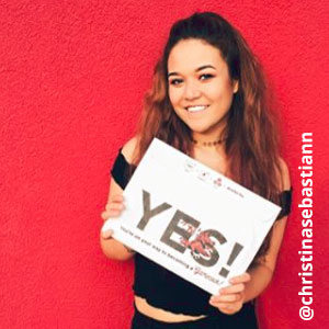 Image provided by @christinasebastiann of a young woman with long, brown hair in front of a red background. She is wearing an off-the-shoulder black top and smiling while she holds an acceptance envelope that says, Yes!