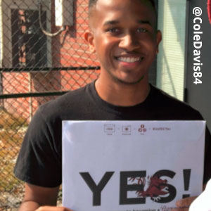 Image provided by @ColeDavis84 of a young man in front of a tall, chain-link fence. He is wearing a black t-shirt and smiling as he holds an acceptance envelope that says, Yes!