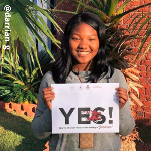 "Image provided by @darrian_g of a young woman with black hair, smiling and holding an acceptance envelope that says, ""Yes!"" She is standing outside on a green lawn wearing a grey shirt."