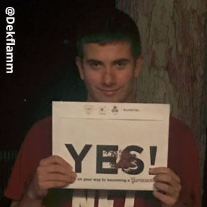 Image provided by @Dekflamm_ of a young man smiling and holding an acceptance envelope beneath his chin that says, Yes!