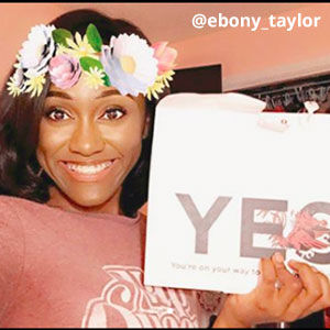 Filtered image provided by @ebony_taylor of a young woman with a flower crown. She is smiling and holding an acceptance envelope that says, Yes!