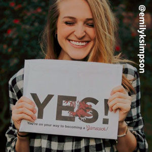 Image provided by @emilyksimpson of a young, blonde woman grinning with her eyes closed and holding an acceptance envelope under her chin that says, Yes!