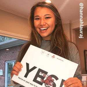 Image provided by @hannahlauraj of a young woman with long, brown hair wearing a grey shirt. She is smiling and holding an acceptance envelope that says, Yes!