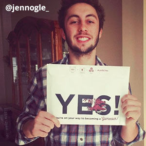 Image provided by @jennogle_ of a young, man smiling and holding an acceptance envelope that says, Yes! He is bearded with brown hear.