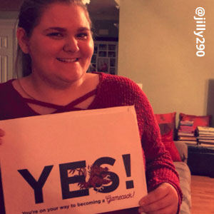 Image provided by @jilly290 of a young woman with her hair pulled back. She is wearing a red, long-sleeved sweater and smiling while she holds an acceptance envelope that says, Yes!