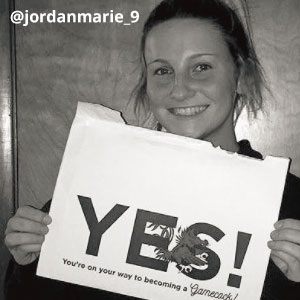 Black-and-white image of @jordanmarie_9 smiling and holding an acceptance envelope under her chin that says, Yes!