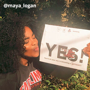 "Image provided by @maya_logan of a young woman holding an acceptance envelope that says, ""Yes!"" and blowing it a kiss. She is outside, wearing a black t-shirt that says, Carolina Gamecocks."