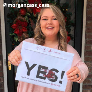 Image provided by @morgancass_cass of a young, woman with curled blonde hair and dimples. She stands in front of a wreath with red flowers, wearing a pink blouse. She smiling while she holds up an acceptance envelope that says, Yes!
