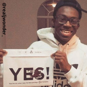 Image provided by @realjwonder_ of a young man in glasses and a hooded, white Adidas sweatshirt. He has a black hat turned to the back. He is  grinning proudly and holding an acceptance envelope that says, Yes!