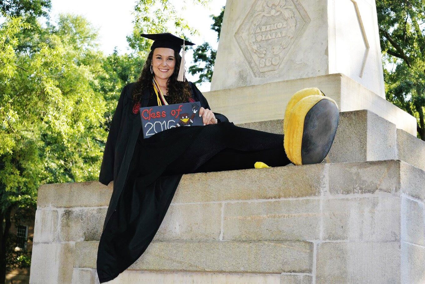 Graduating female senior poses on the Maxcy monument with her Cocky mascot feet on.