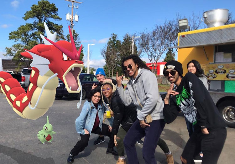 Group of students next to Pokemon monsters