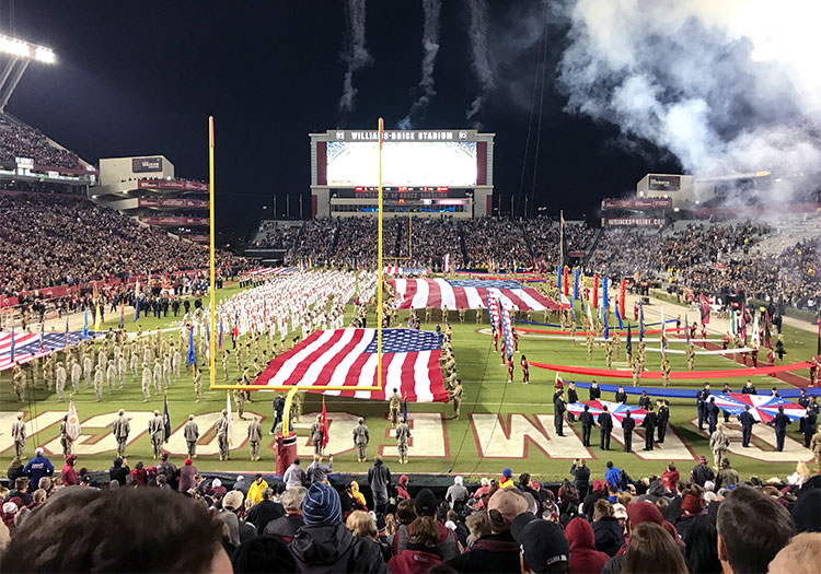 Williams-Brice stadium with band and flags on field.