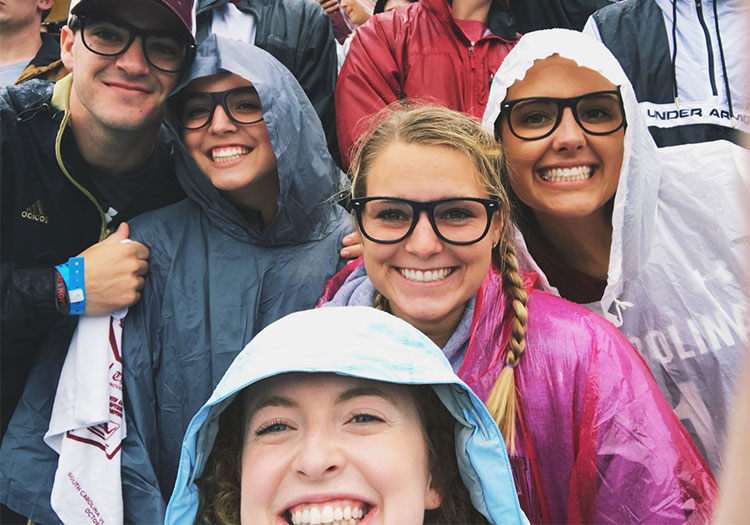 Group of students wearing glasses in rain at football game.