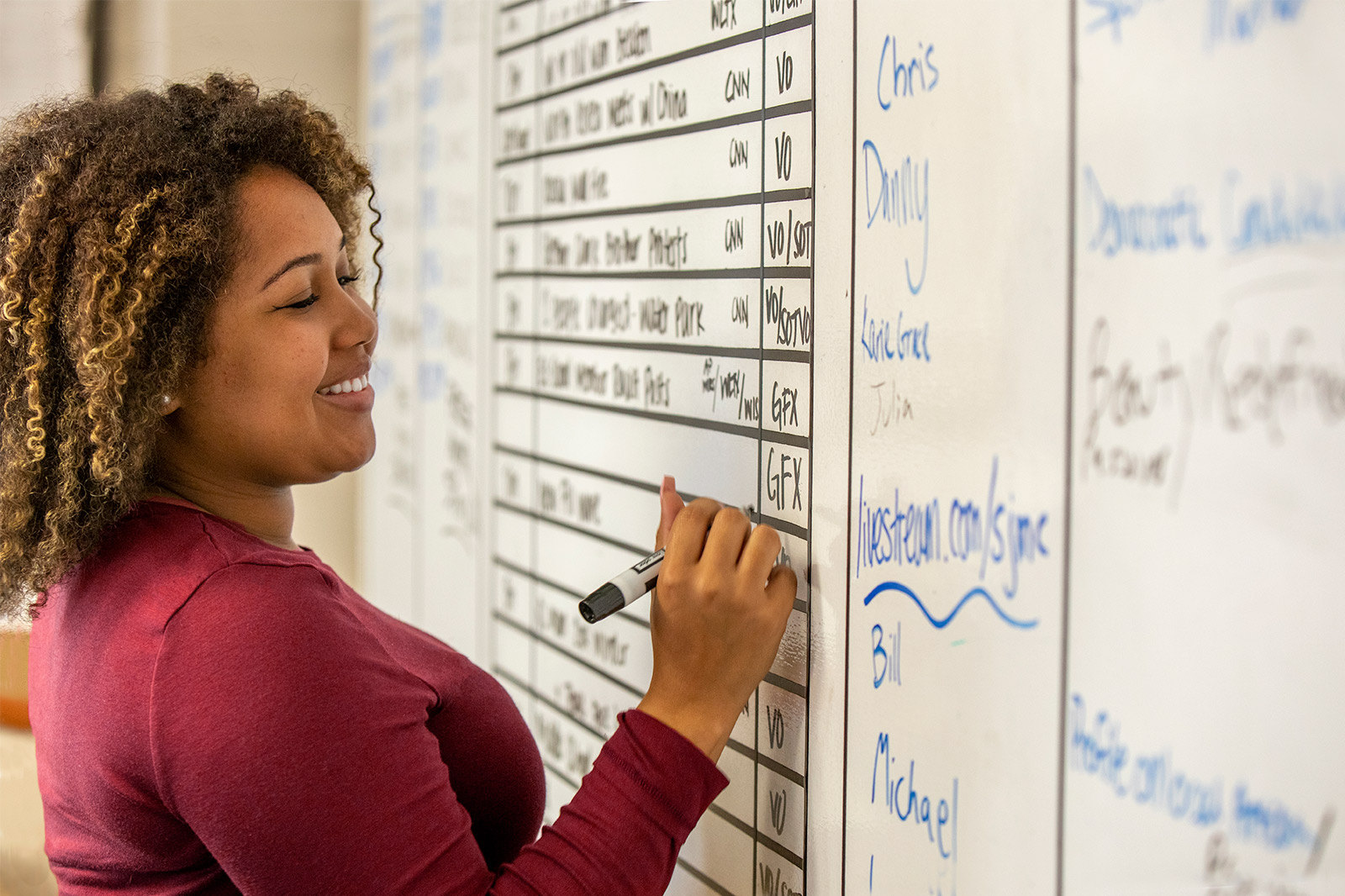 A journalism student smiles while filling in the day's television news production schedule on a dry erase board.
