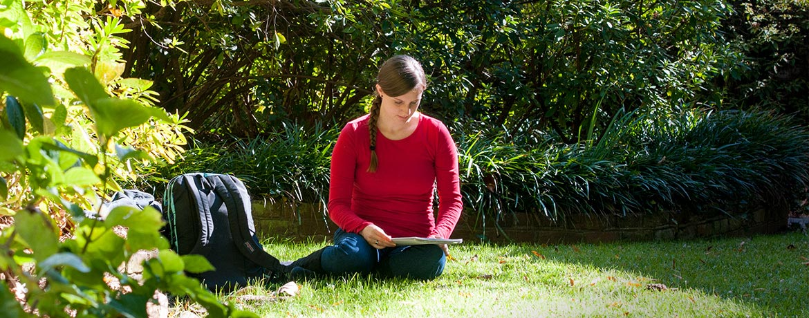student studying outdoors on campus surrounded by lush greenery