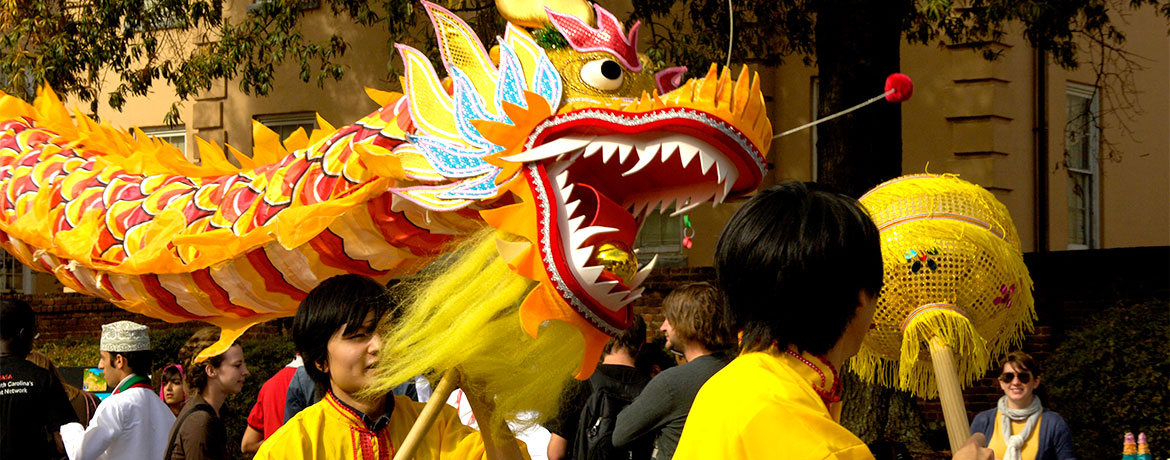 students carry a bright yellow dragon as part of the international parade down Greene Street
