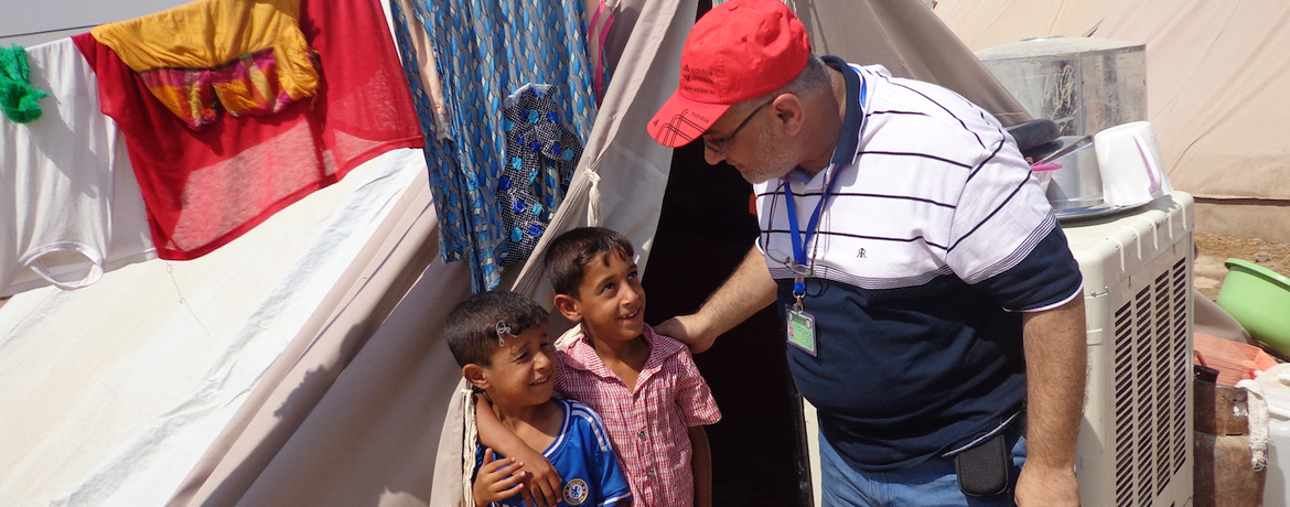 professor talking to two young children at a shelter