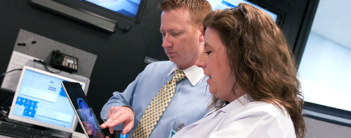two people consulting digital body scan images on a tablet