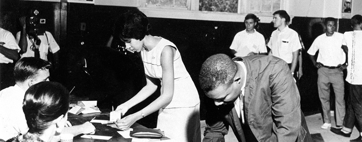 black students signing forms at a table while a news camera films